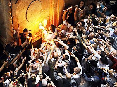 Патриарх подаёт пучки свечей чрез окошко